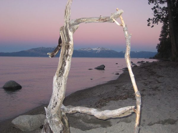 A rocky shore at Lake Tahoe looking toward peaks at Donner Pass through a driftwood frame